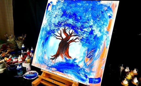Painting orange tree trunk and blue leaves on abstract background